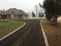 Recycled asphalt drive with concrete border.